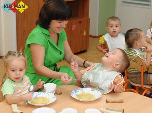 воспитатель кормит детей в яслях