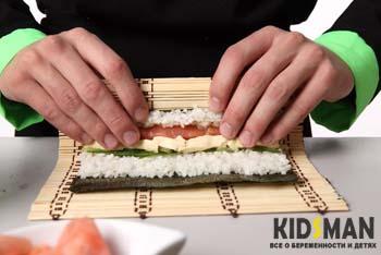 мужчина готовит суши