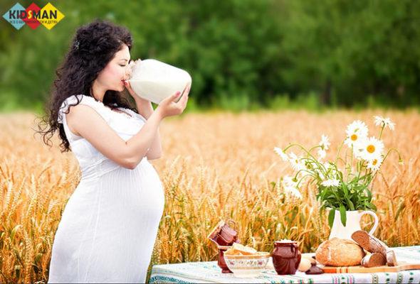 беременная женщина пьет молоко из кувшина