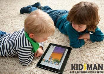 два ребенка смотрят на планшет