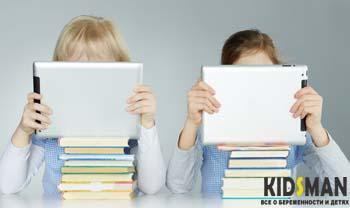 два ребенка читают на планшете