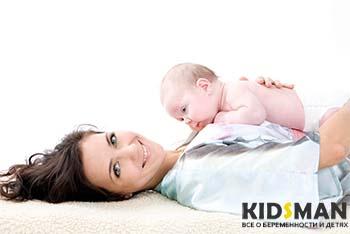 ребенок лежит на матери