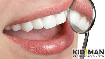 девушка смотрит зубы в зеркале