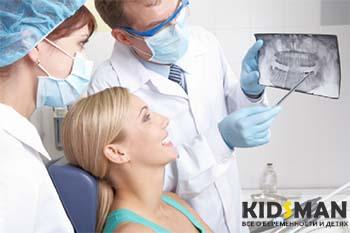 врачи показывают пациенту рентген зубов