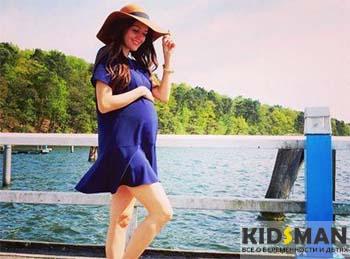 беременная женщина стоит на пирсе