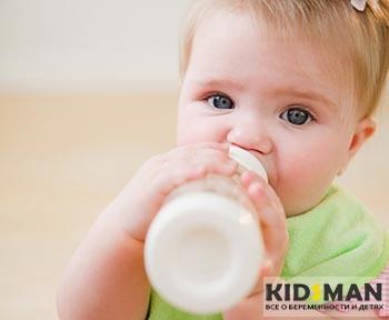девочка пьет молоко из бутылочки