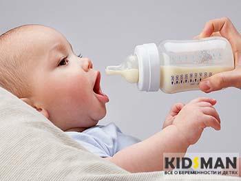 младенец ест смесь из бутылочки