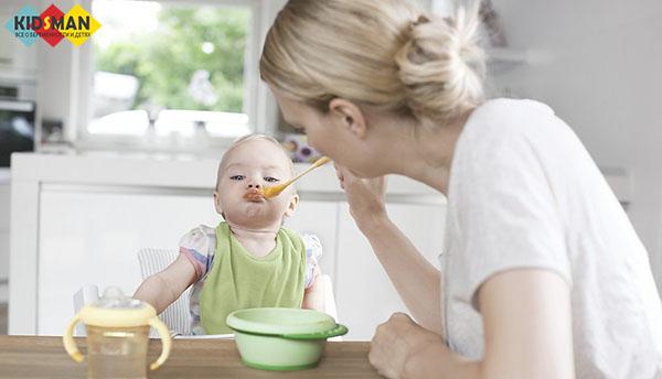 мама кормит ребенка рисовой кашей