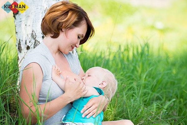 кормит грудью ребенка на природе