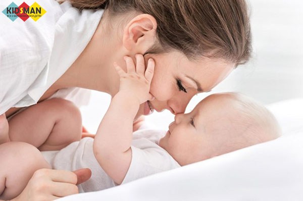 мама играет с новорожденным ребенком